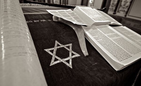a copy of the Torah and a shofar lie on a cloth embroidered with the Star of David
